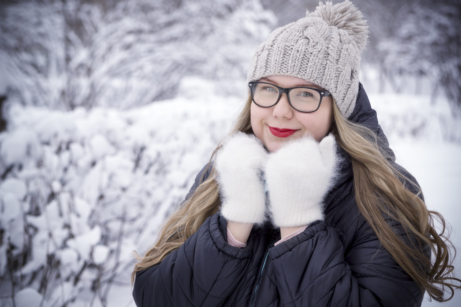 Young lady wearing new glasses in a winter scene